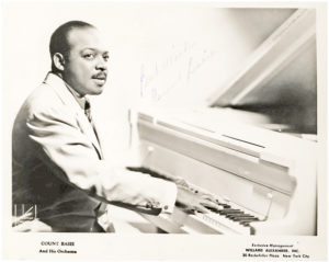 33835Photograph of Count Basie Seated at His White Piano